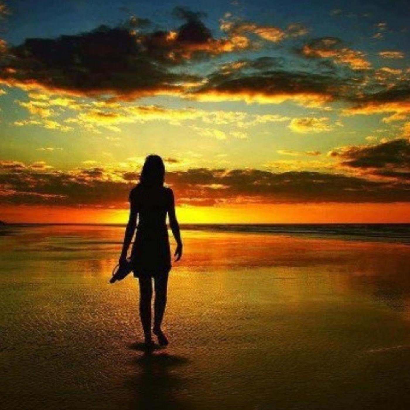 Фото силуэт девушки которая стоит на берегу моря на закате